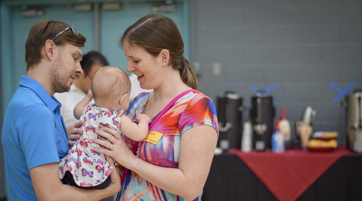 ASU student Olivia Rines holds her infant baby with her husband