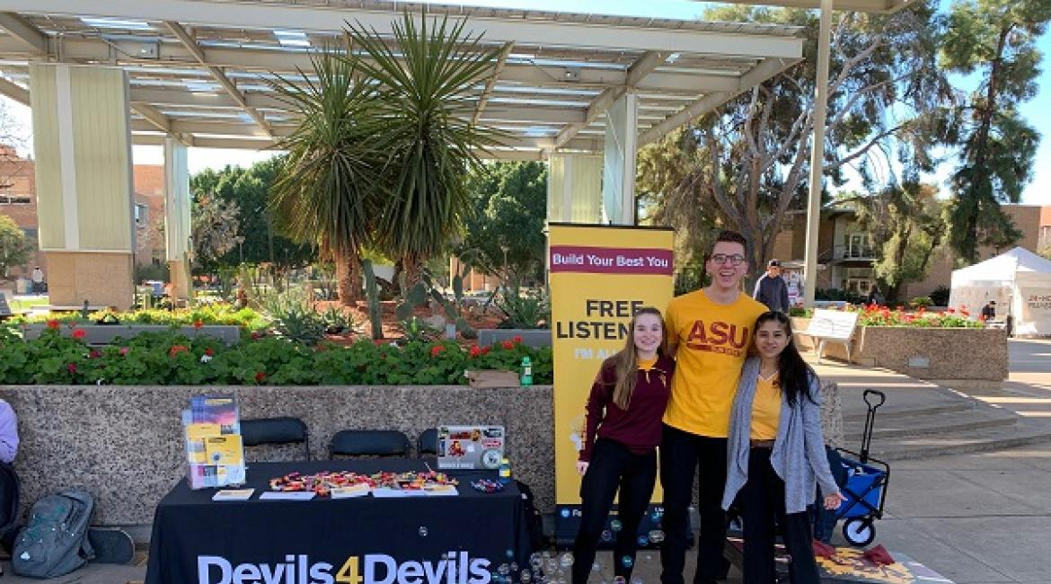 Three ASU students in front of a Devils 4 Devils table with a bubble machine