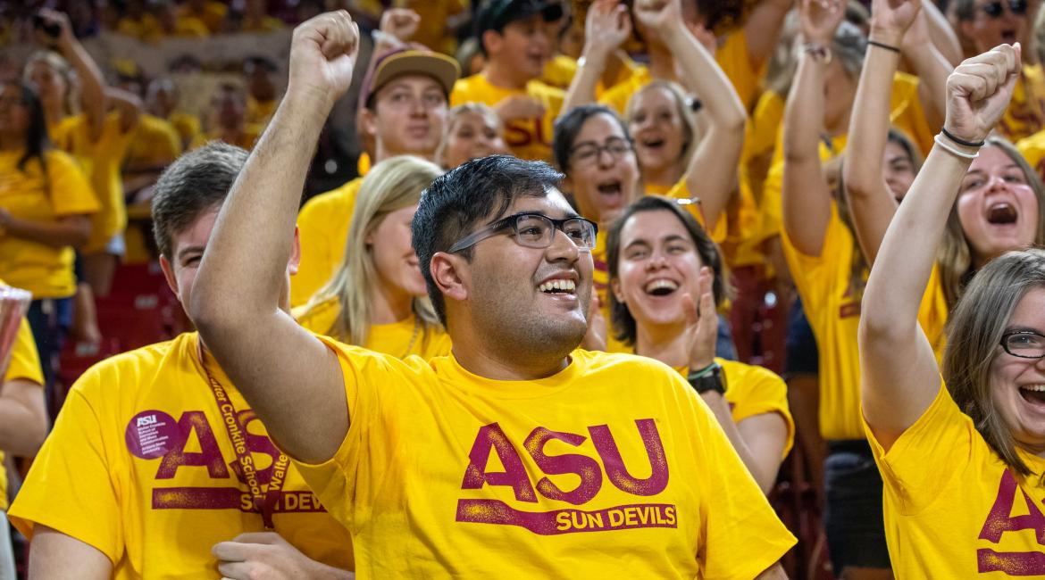First-year students in gold ASU shirts raise their arms and cheer at the ASU Welcome event on Aug. 20, 2019, at Wells Fargo Arena in Tempe, Ariz.