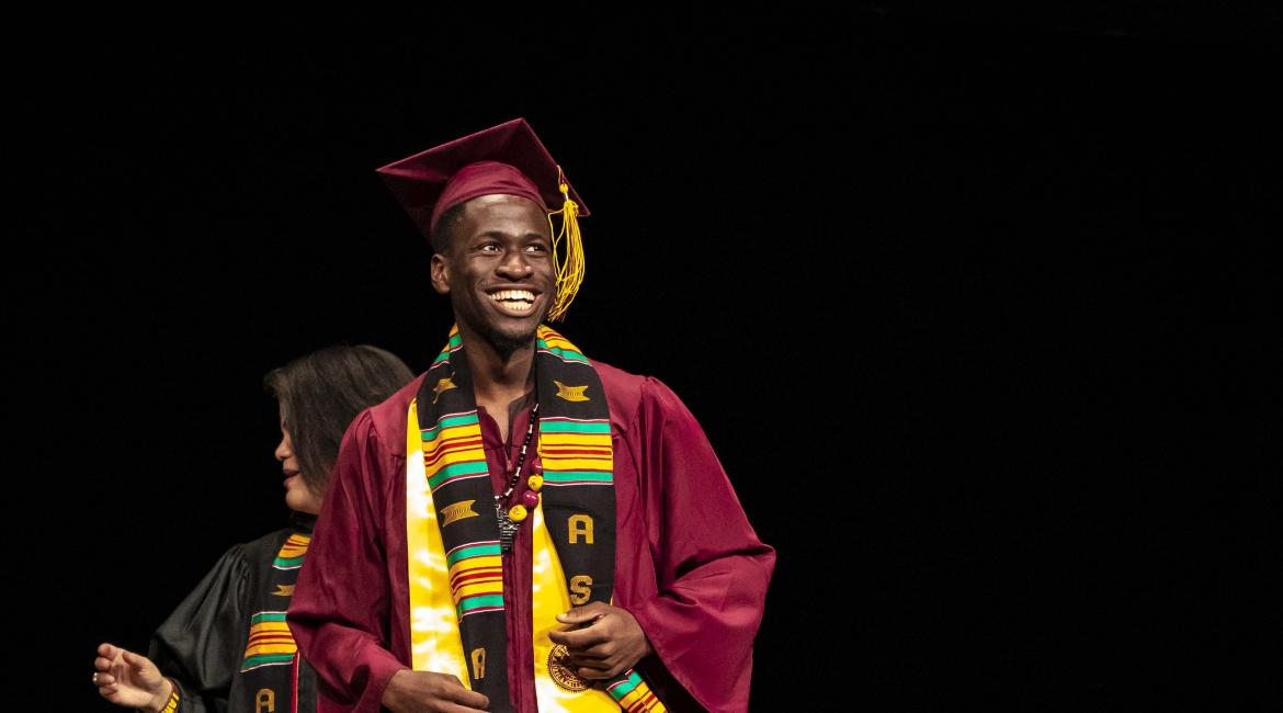ASU Black African Convocation male graduate onstage with his stole and cap and gown