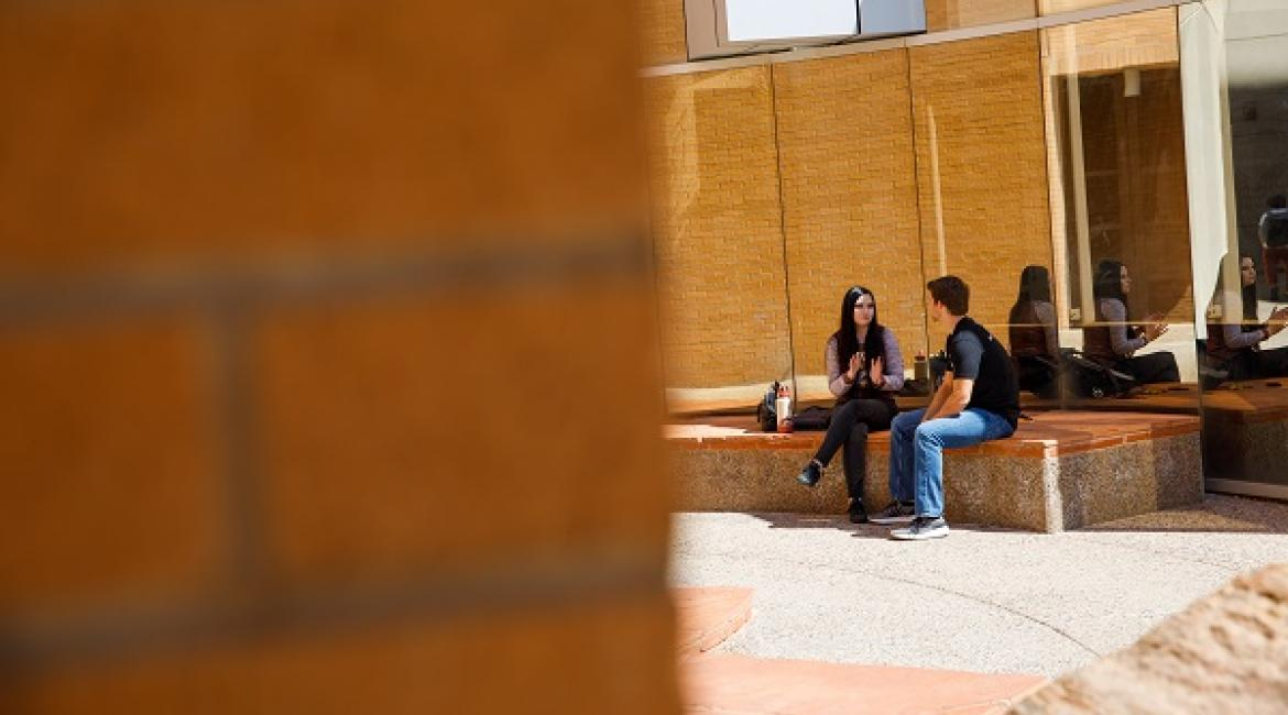 Two students talking and sitting