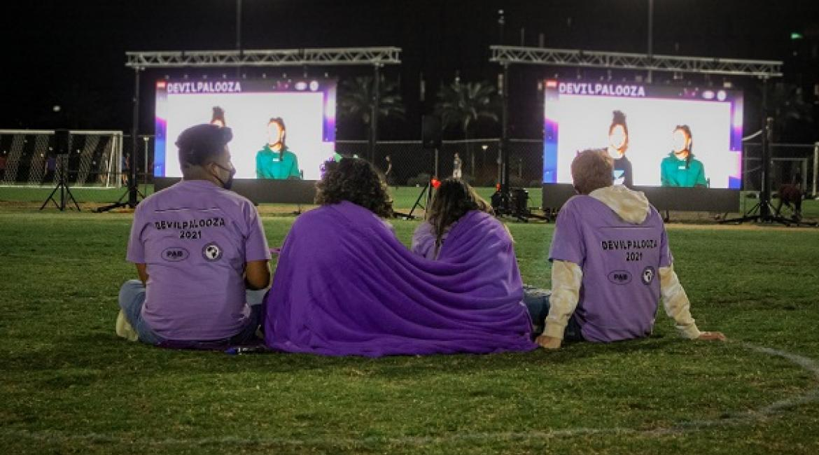 Students on a lawn in front of two large screens at Devilpalooza 2021 at ASU Tempe SDFC Fields