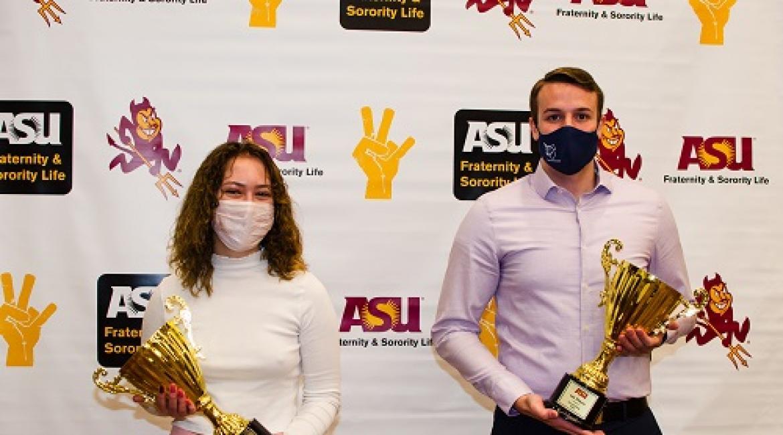 Two masked ASU students with Greek Week trophies