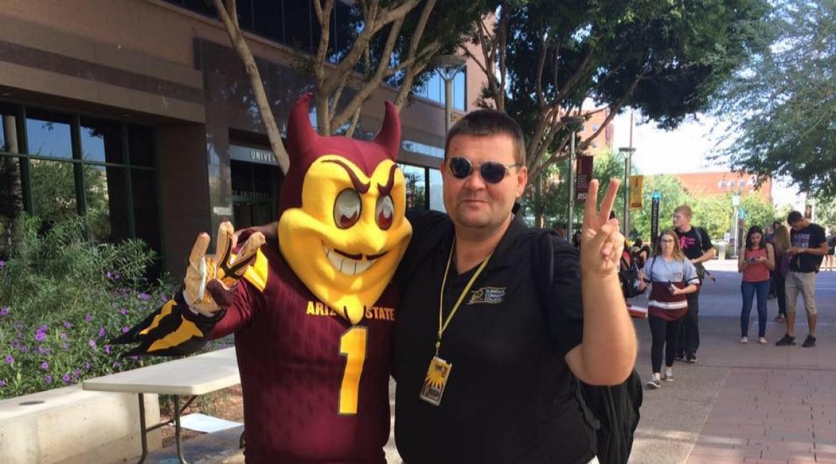 ASU grad James Deibler poses with Sparky at the downtown campus.