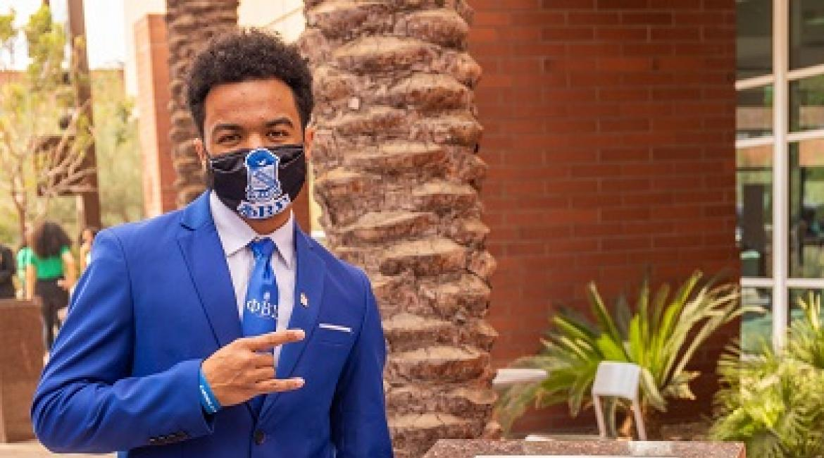 ASU student Style Ranger in a blue suit and mask next to the Phi Beta Sigma NPHC Plot
